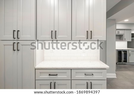 Gray kitchen built with shaker style cabinets and white quartz countertop. Shows stainless steel appliances, white brick subway tile back splash and  under cabinet lights. Royalty-Free Stock Photo #1869894397