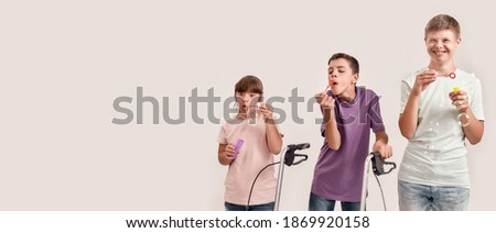 Three cheerful disabled children with Down syndrome and cerebral palsy smiling while blowing soap bubbles, standing together isolated over white background. Lifestyle of special children concept Royalty-Free Stock Photo #1869920158
