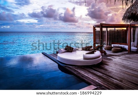 Luxury beach resort, bungalow near endless pool over sea sunset, evening on tropical island, summer vacation concept #186994229