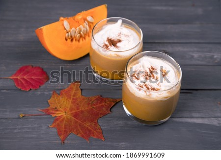 Two glasses of pumpkin latte with cream and cinnamon and a piece of sliced pumpkin on a dark wooden background. Autumn drink