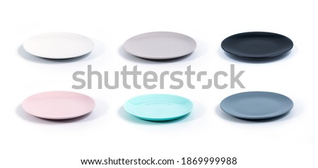 Set of six colorful empty plates isolated on white background side view, selective focus. White, Grey, Black, Pink, Turquoise and Navy Blue empty plates collection Royalty-Free Stock Photo #1869999988