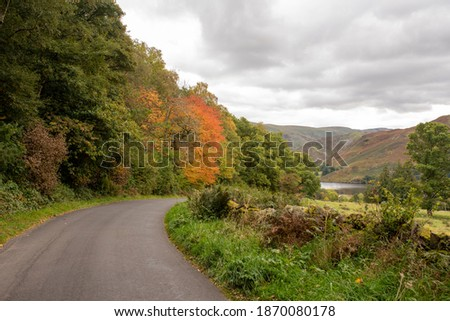 Beautiful Tree Lined Winding Road Leading down to Ullswater Lake in Autumn. 2020 Royalty-Free Stock Photo #1870080178