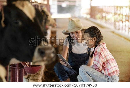 Asian woman and young girl use tablet teaching how to feed cow in dairy farm.