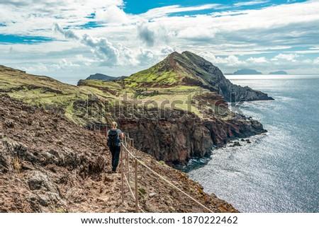 Girl hiking rocky cliffs clear near water of Atlantic Ocean bay Ponta de Sao Lourenco, the island of Madeira, Portugal Royalty-Free Stock Photo #1870222462