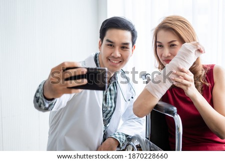 Selfie of smiling man doctor with a female patient wear arm splint for better healing sit in a wheelchair using a smartphone In the room hospital background.