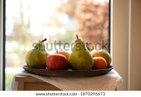 A selection of colourful ripe fruits on a wooden tray. Autumn Boca background. Light wood stool. White cotton kitchen towel. Organic fruits: pears, apple,  clementine, grapefruit, orange. Still life #1870296673