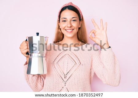 Young brunette woman holding italian coffee maker doing ok sign with fingers, smiling friendly gesturing excellent symbol
