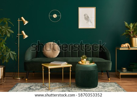 Luxury living room in house with modern interior design, green velvet sofa, coffee table, pouf, gold decoration, plant, lamp, carpet, mock up poster frame and elegant accessories. Template.  Royalty-Free Stock Photo #1870353352