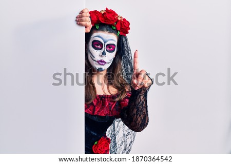 Young woman wearing day of the dead custome holding blank empty banner pointing with finger up and angry expression, showing no gesture