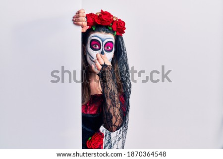 Young woman wearing day of the dead custome holding blank empty banner smelling something stinky and disgusting, intolerable smell, holding breath with fingers on nose. bad smell