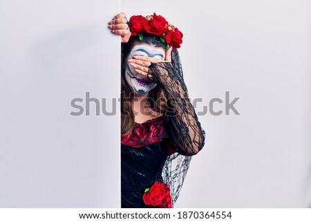 Young woman wearing day of the dead custome holding blank empty banner smiling and laughing with hand on face covering eyes for surprise. blind concept.