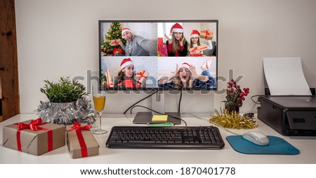 People on virtual call with family and friends exchanging gifts and celebrating virtual christmas online due to social distancing and coronavirus lockdown and quarantines. Image on computer screen.
