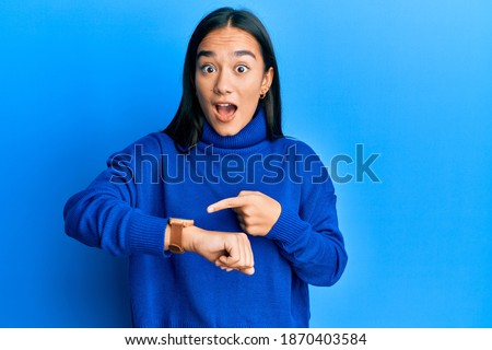 Young asian woman wearing casual winter sweater in hurry pointing to watch time, impatience, upset and angry for deadline delay  Royalty-Free Stock Photo #1870403584