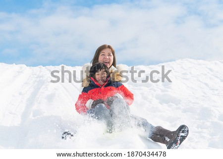 Asian mother and her son  sliding on sleds down snow hill in winter