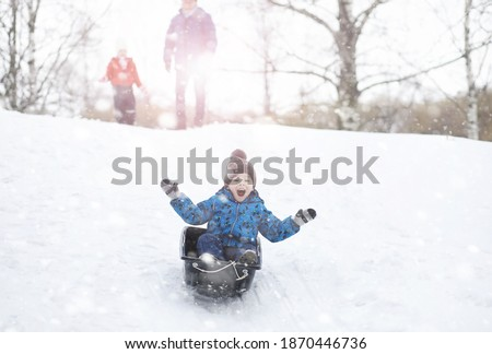 Children in the park in winter. Kids play with snow on the playground. They sculpt snowmen and slide down hills. Royalty-Free Stock Photo #1870446736