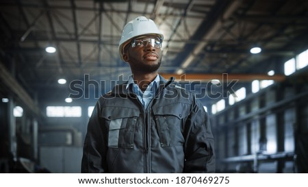 Portrait of Professional Heavy Industry Engineer Worker Wearing Uniform, Glasses, Hard Hat in Steel Factory. Smiling African American Industrial Specialist Standing in Metal Construction Manufacture. Royalty-Free Stock Photo #1870469275