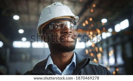 Happy Professional Heavy Industry Engineer Worker Wearing Uniform, Glasses and Hard Hat in a Steel Factory. Smiling African American Industrial Specialist Standing in a Metal Construction Manufacture. Royalty-Free Stock Photo #1870469278