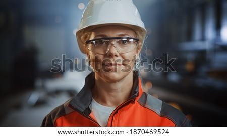 Portrait of a Professional Heavy Industry Engineer Worker Wearing Uniform, Glasses and Hard Hat in a Steel Factory. Beautiful Female Industrial Specialist Standing in Metal Construction Facility. Royalty-Free Stock Photo #1870469524