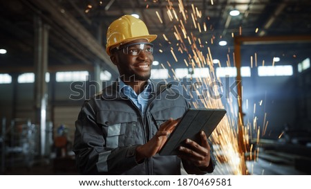 Professional Heavy Industry Engineer Worker Wearing Safety Uniform and Hard Hat Uses Tablet Computer. Smiling African American Industrial Specialist Standing in a Metal Construction Manufacture. Royalty-Free Stock Photo #1870469581