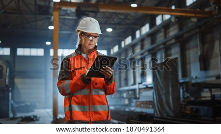 Professional Heavy Industry Engineer Worker Wearing Safety Uniform and Hard Hat, Using Tablet Computer. Serious Successful Female Industrial Specialist Walking in a Metal Manufacture Warehouse. Royalty-Free Stock Photo #1870491364