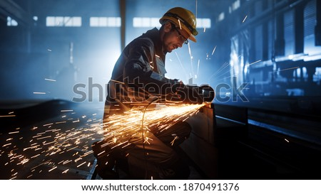 Heavy Industry Engineering Factory Interior with Industrial Worker Using Angle Grinder and Cutting a Metal Tube. Contractor in Safety Uniform and Hard Hat Manufacturing Metal Structures. Royalty-Free Stock Photo #1870491376