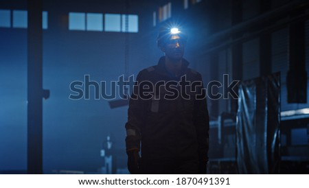 Professional Heavy Industry Engineer Worker Wearing Uniform, Flashlight on the Hard Hat in a Steel Factory. Industrial Specialist Walking Towards the Camera in a Dark Metal Construction Manufacture. Royalty-Free Stock Photo #1870491391