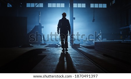 Professional Heavy Industry Engineer Worker Wearing Uniform, Flashlight on the Hard Hat in a Steel Factory. Industrial Specialist Walking Towards the Camera in a Dark Metal Construction Manufacture. Royalty-Free Stock Photo #1870491397