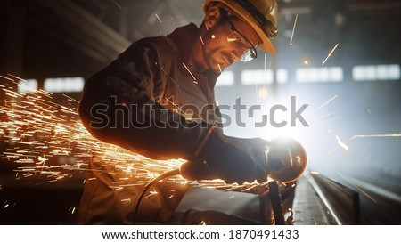 Heavy Industry Engineering Factory Interior with Industrial Worker Using Angle Grinder and Cutting a Metal Tube. Contractor in Safety Uniform and Hard Hat Manufacturing Metal Structures. Royalty-Free Stock Photo #1870491433