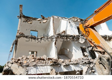 Construction machinery is demolishing the house. Royalty-Free Stock Photo #1870554733