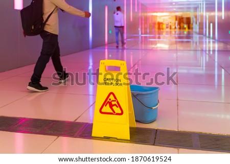 """Caution wet floor"" sign in mall"