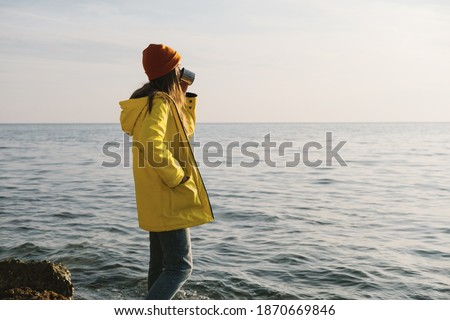 Young beautiful woman in bright yellow illuminating coat stands on the ultimate grey seashore or ocean. Concept of freedom, thoughtfulness, mindfulness. Color of te year 2021.
