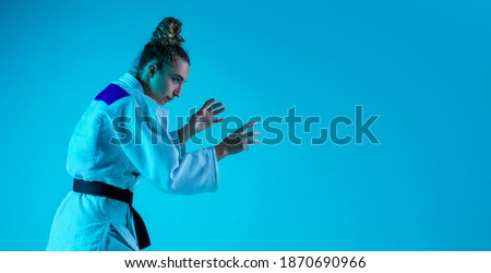 View from side. Professional female judoist in white judo kimono practicing and training isolated on blue neon background. Grace of motion and action. Healthy lifestyle, sport and movement concept. Royalty-Free Stock Photo #1870690966