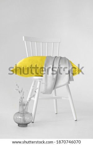 Minimalistic background in trending 2021 colors. Gray and yellow. A chair with a yellow pillow against a gray wall.