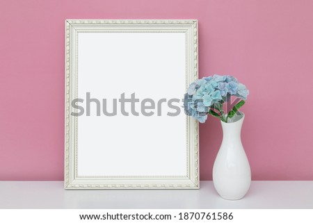 Empty mock up wooden frame with vase and hydrangea: a fragment of the interior for your painting, photo, poster, motivational quote