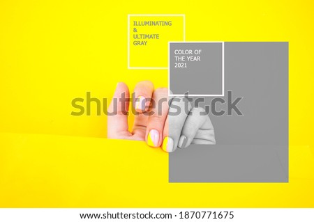 Young woman's hand with beautiful manicure on illuminating yellow and gray color background holding bright yellow paper. Color 2021. Royalty-Free Stock Photo #1870771675