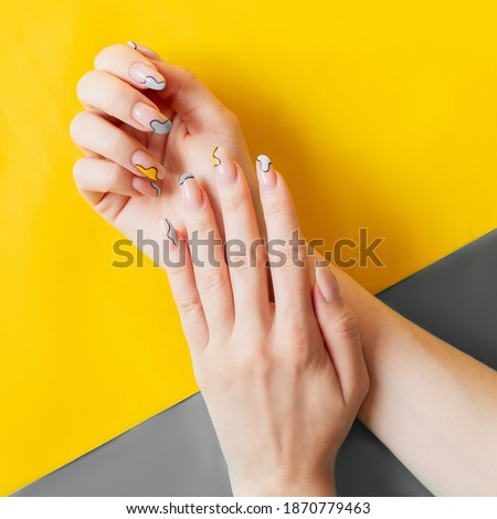 Beautiful trendy art manicure gray and yellow. Color of the year 2021. Acrylic nails gel polish creative design. Illuminating  Ultimate Gray Royalty-Free Stock Photo #1870779463
