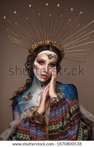 Portrait of a girl with gold and blue creative art make-up. Photo taken in the studio. Renaissance Royalty-Free Stock Photo #1870800538
