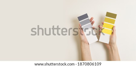 Women's hands hold swatches of the trendy colors - illuminating yellow and ultimate grey. Selection of year 2021 colors for design of clothes, interiors, websites and publications. Flat lay.