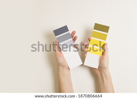 Women's hands hold swatches of the trendy colors - illuminating yellow and ultimate grey. Selection of year 2021 colors for design of clothes, interiors, websites and publications. Flat lay.  Royalty-Free Stock Photo #1870806664