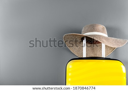 Bright and stylish yellow cabin size suitcase with straw hat against trendy gray background. Easy travel with little baggage concept. Copy space. trendy colors of 2021