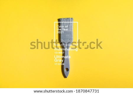 Grey brush on yellow background, trend and mod colors of 2021 year. Minimalistic vibrant picture for article, banner or poster. Ultimate Gray and Illuminating Royalty-Free Stock Photo #1870847731