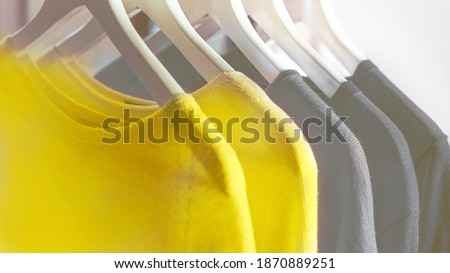 Bright illuminating yellow and gray colours clothes on hangers. Trendy colors of the year 2021 - Gray and Yellow. Fashionable clothes colors. Royalty-Free Stock Photo #1870889251