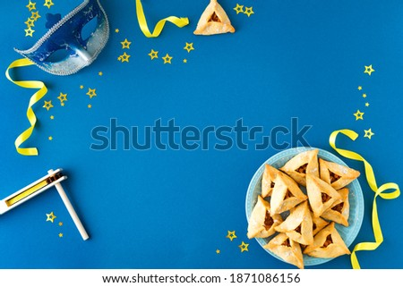 Purim celebration concept (jewish carnival holiday) on blue background, top view, copy space. Purim flat lay with hamantaschen cookies and purim mask.
