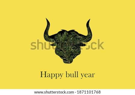 Happy new year and Christmas greeting card in trendy colors. Yellow and gray are the colors of the year 2021. The silhouette of a bull is cut out of paper. Year of the bull.