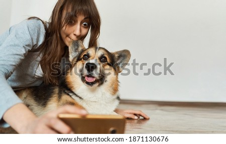 Joyful woman biting fluffy ear her pet Welsh Corgi dog and and taking funny selfie with smartphone camera. Having fun at home together
