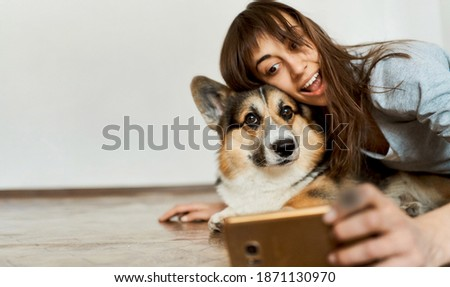 Indoor portrait funny woman and her pet Welsh Corgi dog making selfie photo with smartphone camera. Spending time together at home. Focus on dog nose
