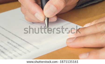 A hand of a man signing a letter. Writing. Hand holding pen.