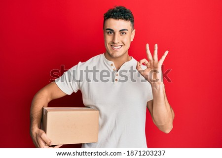 Hispanic young man holding delivery package doing ok sign with fingers, smiling friendly gesturing excellent symbol
