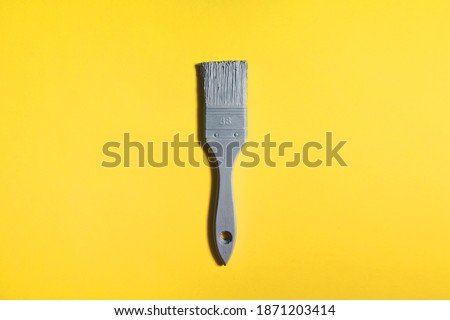 Grey brush on yellow background, trend and mod colors of 2021 year. Minimalistic vibrant picture for article, banner or poster.