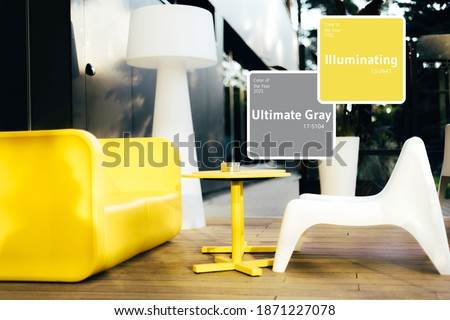 Bright yellow sofa, table against gray wall. Minimalistic style outdoor interior. Demonstrating trendy Color of the Year 2021. Illuminating Yellow and Ultimate Gray. Duotone. Depression treatment.